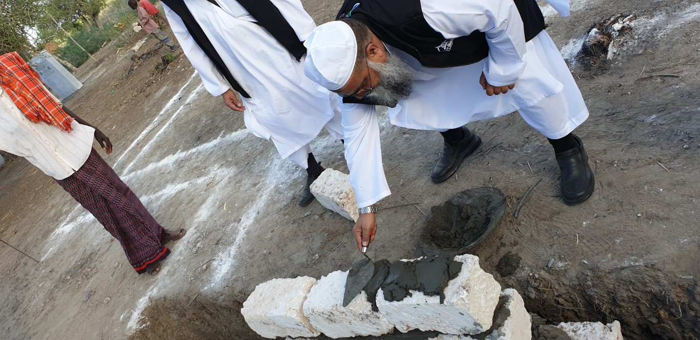 Ml Ahmed Chohan, Al-Imdaad Foundation trustee and Ameer lays bricks in the foundation of one of the key structures