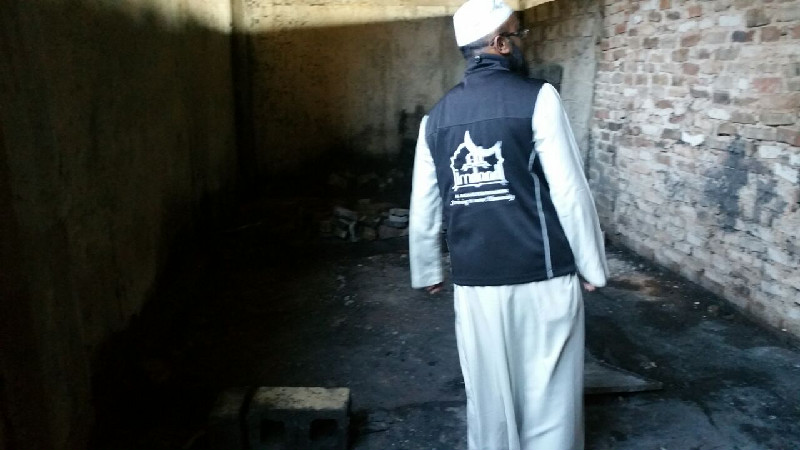 An Al-Imdaad Foundation team member inspects some of the damage caused by the Alexandra fire