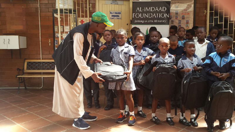 An Al-Imdaad Foundation representative hands over a bag to a young beneficiary