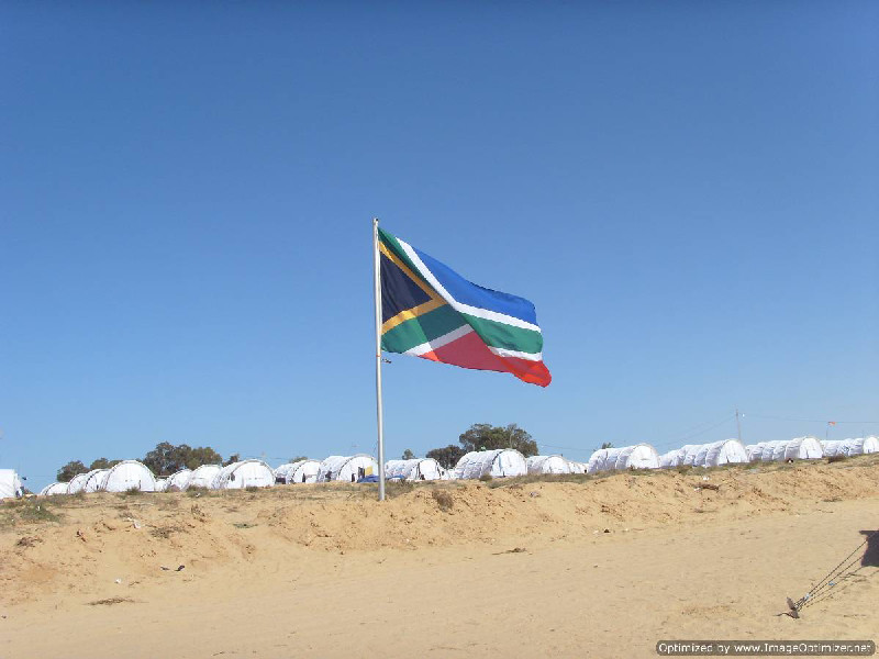 The SA Flag with refugee tents in the background