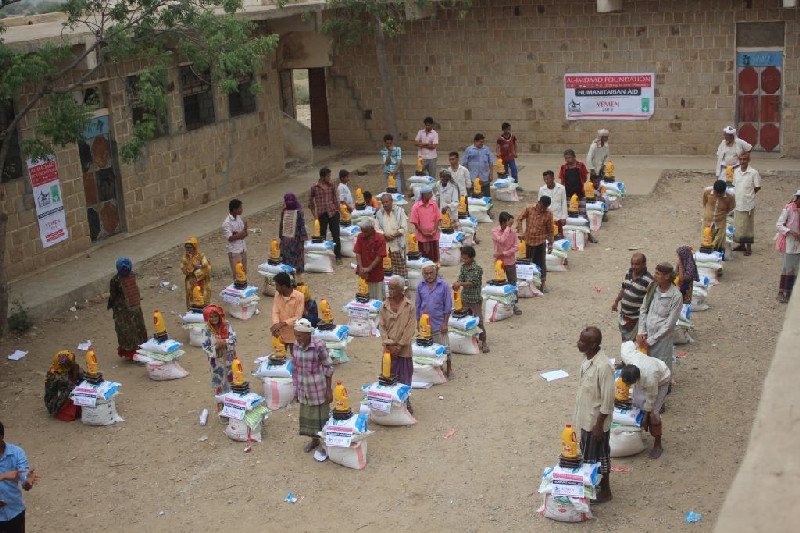 Elderly men from the Wusab governorate collect food hampers for their families