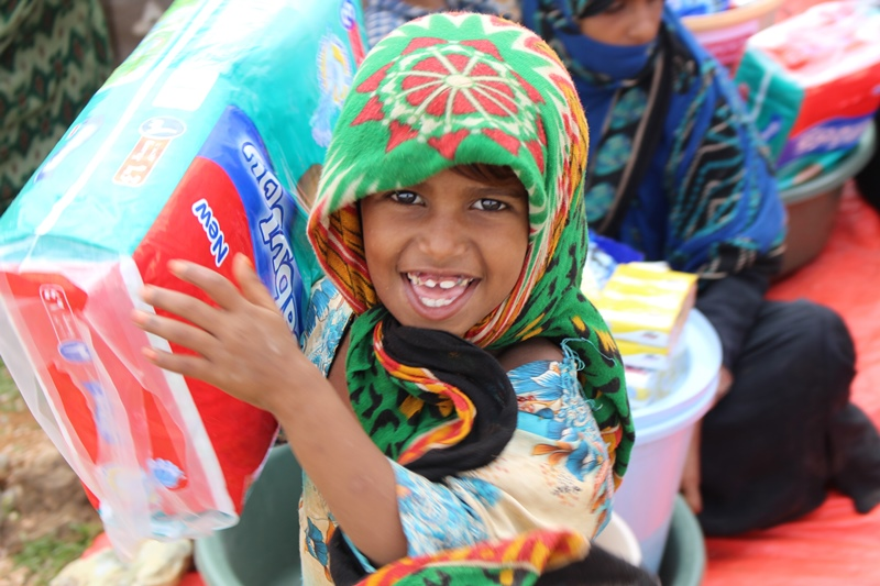 A young girl from Socotra holds up an item from her hygiene pack