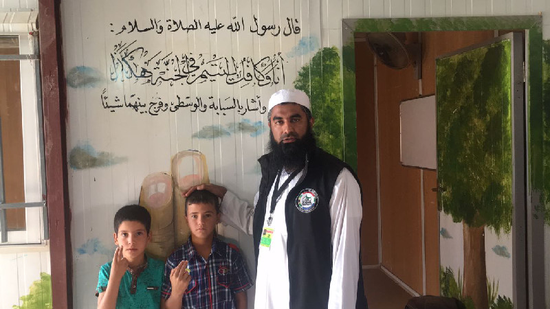 Al-Imdaad Foundation's Moulana Mohamed Motala together with two orphans  in front of a Hadith exalting the status of those who care for orphans